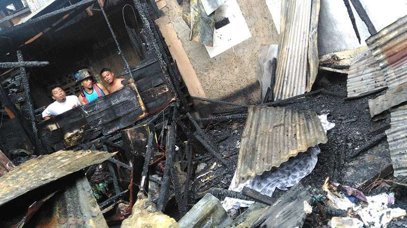 The body of Alexander Sanchez (right below ) covered after fire in Purok 8, Barangay Kamputhaw, Cebu City Friday, February 15.  (Photo courtesy of dyHP)