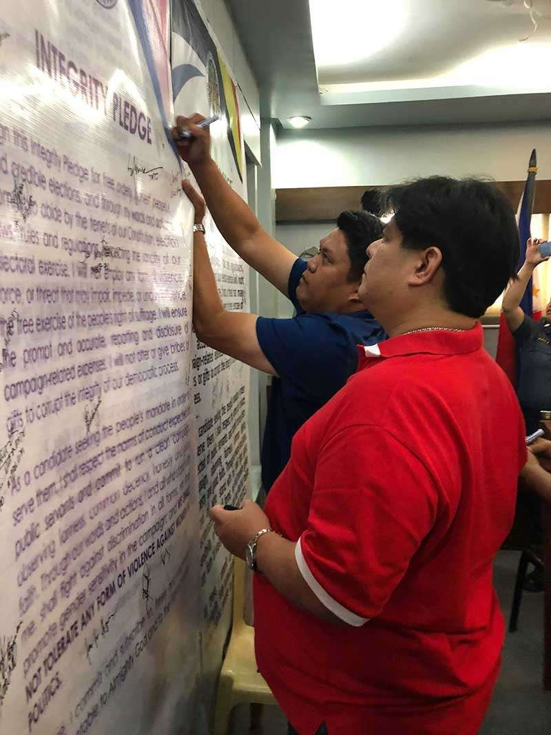 E.B. Mayor Marvin Malacon and Third District Board Member David Lacson sign an integrity pledge during the peace covenant signing held at Negros Occidental Police Provincial Office headquarters in Bacolod City Thursday. (Photo by Glazyl Masculino)