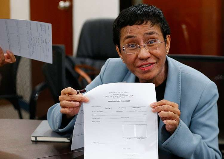 MANILA. Maria Ressa, head of online news site Rappler that has aggressively covered President Rodrigo Duterte's policies, shows an arrest form after being arrested by National Bureau of Investigation agents in a libel case Wednesday, February 13, 2019 in Manila. (AP)