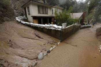 USA. In this January 6, 2016 file photo mud flow skirts a house protected with sandbags in Monrovia, California. Federal forecasters say an El Niño, which alters weather worldwide, has formed but is so weak and late that it shouldn't be a big deal. (AP)