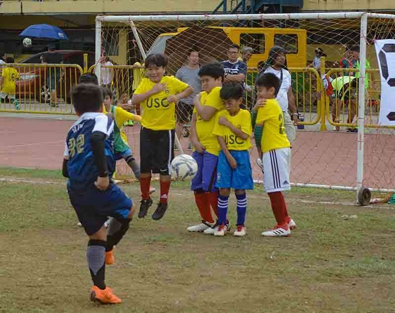 BEND IT. A player from Paref Springdale tries to get past the wall put up by the University of San Carlos during their match in the Sinulog Football Festival. (SunStar Photo / Arni Aclao)
