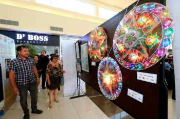 PAMPANGA. City council committee on tourism chairman Councilor Harvey Quiwa and Dr. Lourdes Javier view the colorful lanterns and other displays during Friday's TOFA series exhibition, part of the National Arts Month celebration held at Vista Mall. (Chris Navarro)  onerror=