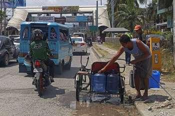 DAVAO. Gipuno sa lalaki ang duha ka butanganan og tubig sakay sa iyang traysikad. Ang tubig gikan sa hose nga way gripo nga anaa sa kilid sa dalan gawas sa opisina sa Department of Health (DOH) sa Jose P. Laurel Avenue, Bajada, Davao City. (Macky Lim)