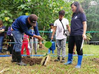 DAVAO. The Philippine Eagle Foundation coordinator shows volunteers how to properly plant and transplant trees. (Lyka Casamayor)