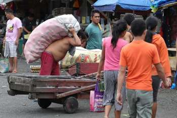 KUSGAN. Wala igsapayan ning usa ka lalaki ang kabug-at sa usa ka sako nga lagutnon nga iyang gikarga aron mahatud sa tindahan sa Bankerohan Public Market sa dakbayan sa Davao. (Mark Perandos)