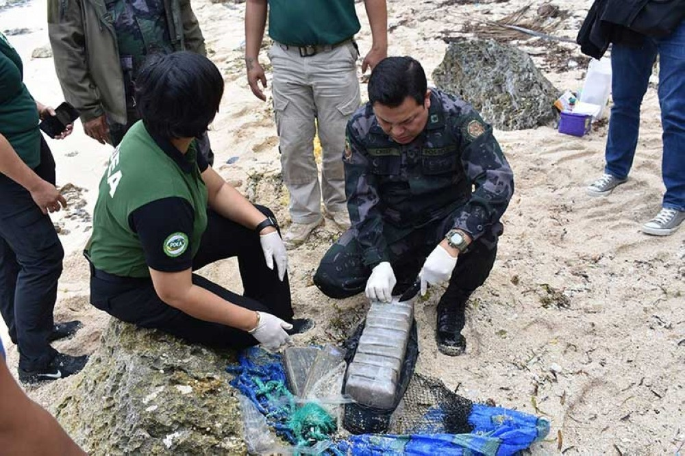 CARAGA. In this file photo, authorities inspect the blocks of cocaine recovered in Surigao del Norte. (Photo courtesy of Caraga Police Public Information Office)
