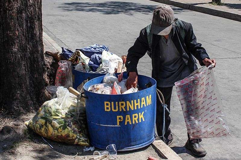 BAGUIO. A man scours trash bins at Burnham Park in search for plastic cups and other recyclables. A kilo of plastic cups is pegged at P15 a kilo. (Photo by Jean Nicole Cortes)