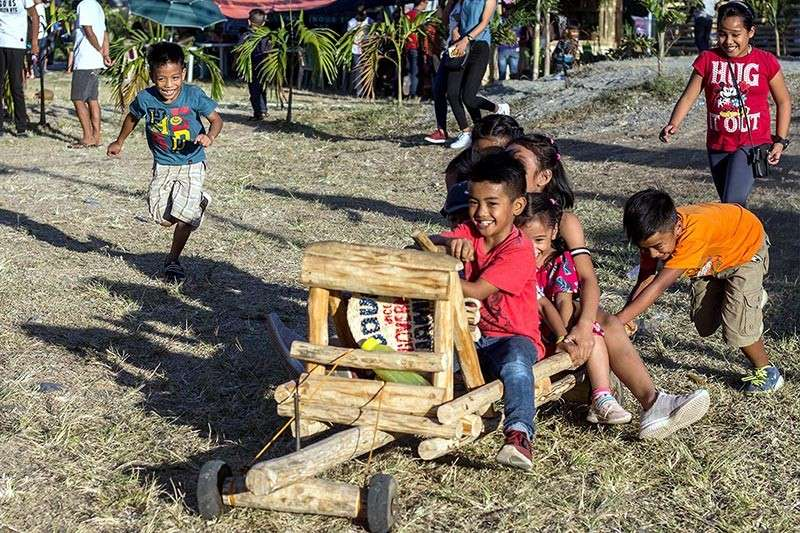 "BAGUIO. A group of children enjoy a ride of ""taltallak,"" an indigenous car made of wood from Lubuagan, Kalinga. (Photo by Jean Nicole Cortes)"