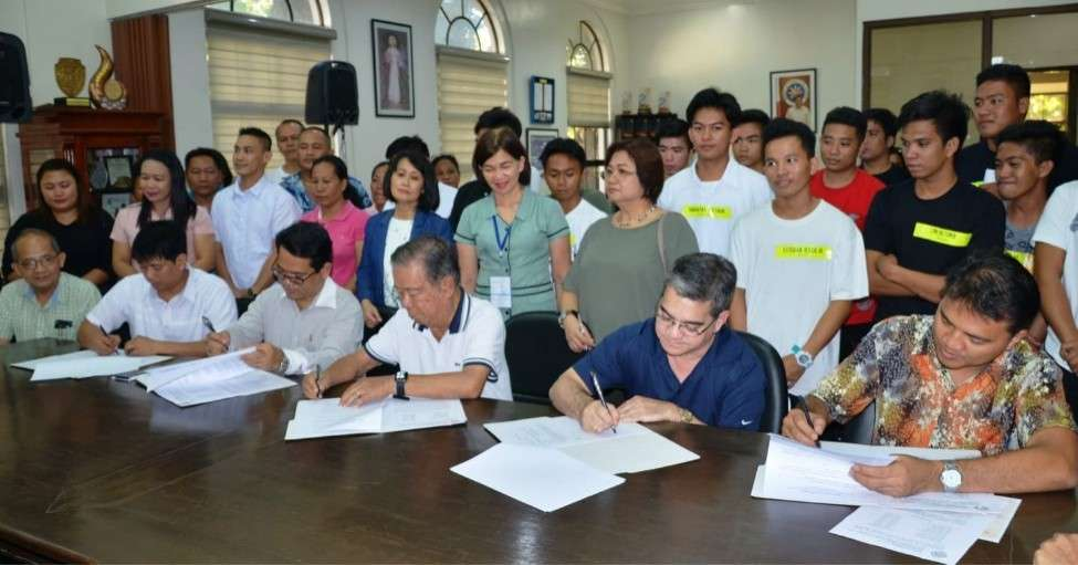 BACOLOD. Governor Alfredo Marañon Jr. (seated, 3rd from right) and Dualtech Training Center Foundation Inc. executive director Jerry Webb Muhi and registrar Rodolfo Sta. Ana III, along with Buglas Foundation Inc. representatives, DepEd Negros Occidental Schools Division Superintendent Portia Mallorca, Provincial Planning and Development Officer Marlin Sanogal, and Provincial Scholarship head Karen Dinsay, scholars, and parents during the MOA signing ceremony for a techvoc scholarship program at the Provincial Capitol in Bacolod City Wednesday, February 20, 2019. (Capitol PIO)
