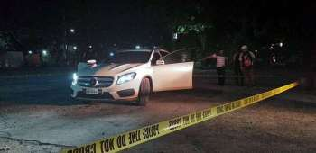BACOLOD. Police cordon the area where a Filipino-Chinese businessman and his wife onboard a white Mercedes Benz were shot by unidentified motorcycle-assailants inside the compound of Redemptorist Church in Barangay 5, Bacolod City, Tuesday night, February 19, 2019. (Contributed Photo) onerror=