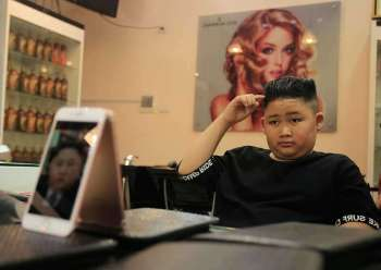VIETNAM. To Gia Huy, 9, checks his hair after having a Kim Jong Un haircut in Hanoi, Vietnam, on Tuesday, Feb. 19, 2019. (AP)