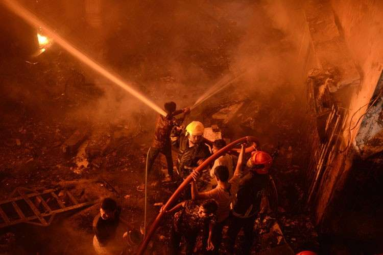 BANGLADESH. In this Wednesday, February 20, photo, firefighters try to douse flames in Dhaka, Bangladesh. A devastating fire raced through at least five buildings in an old part of Bangladesh's capital and killed scores of people. (AP Photo)