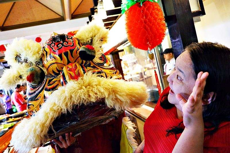 DAVAO. Edith Regalado greets Lion dance performer for good luck. (Joji Alcantara)