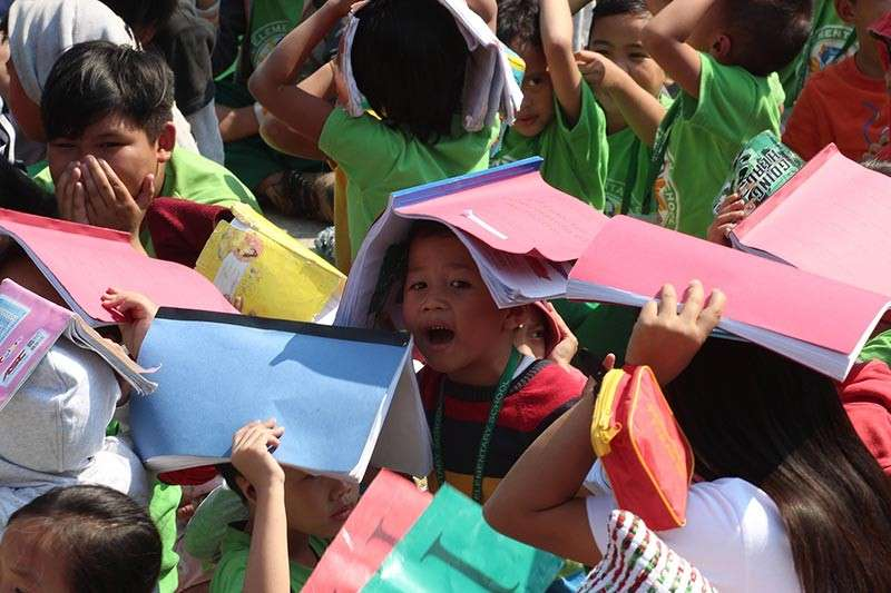 BAGUIO. Students and teachers of Rizal Elementary school cover their heads with books to protect themselves during the first quarter simultaneous earthquake drill on February 21. (Photo by Jean Nicole Cortes)