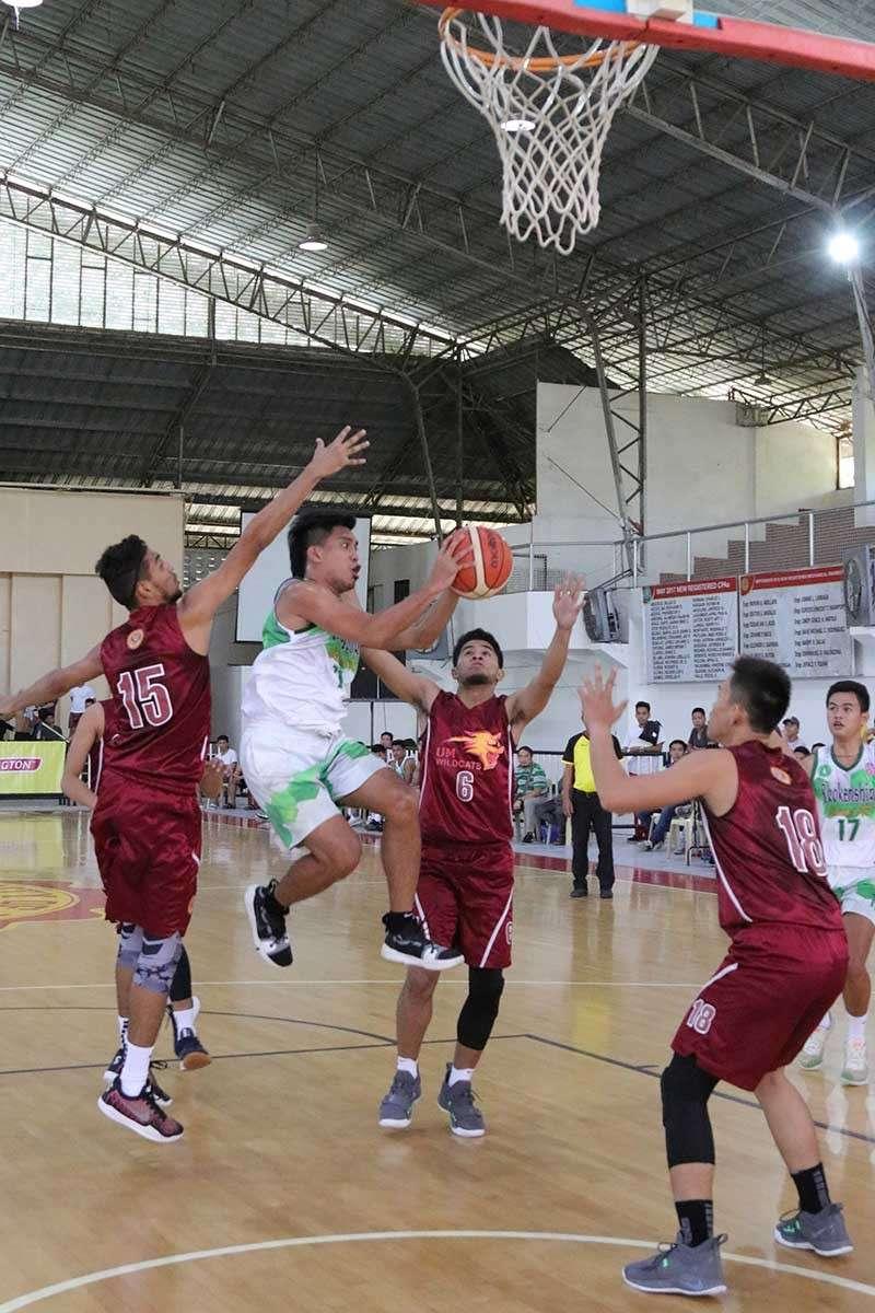 DAVAO. A Brokenshire College player drives to shoot against three University of Mindanao (UM) Wildcats defenders. UM wins, 78-59. (Mark Perandos)