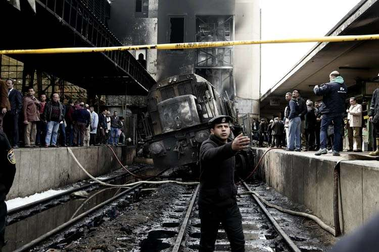 EGYPT. Policemen stand guard in front of a damaged train inside Ramsis train station in Cairo, Egypt, Wednesday, February 27. An Egyptian medical official said at least 20 people have been killed and dozens injured after a railcar rammed into a barrier inside the station causing an explosion of the fuel tank and triggering a huge blaze that engulfed that part of the station. The head of the Cairo Railroad Hospital said the death toll is expected to rise further. (AP Photo)