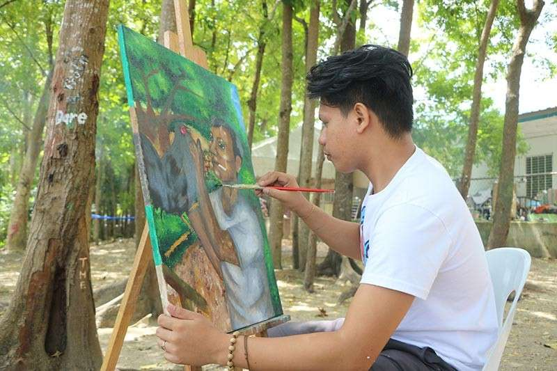 LITERARY YOUNG AT ART. Grade 12 student Johnmark S. Rebato puts finishing touches on his artwork that will be on display on March 8. (Photo by Giselle Abalos)
