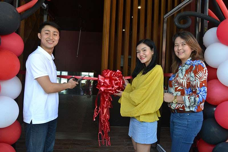 DAVAO. (From left) 4th Street Cafe owner Joenar Bryan H. Ponce; Tawag Tanghalan three-time defending champion Janine Cartagena; and Gemima Valderrama, author and AB Mass Communication adviser at the Ateneo de Davao University during the ribbon cutting of the new store of the cafe. (Reuel John F. Lumawag)