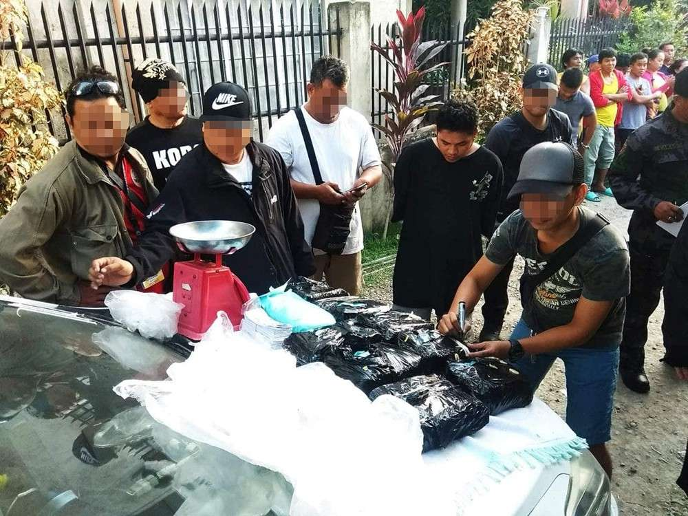 MAJOR HAUL. Some 18 kilos of shabu worth P122.4 million are seized from Elymar Ancajas (in black shirt) in Inayawan, Cebu City on Sunday, March 3. He points police to his source, resulting in the seizure of 10 more kilos of shabu worth P68 million. Police also arrest Jocelyn Encila and her parents. (Contributed foto / Cebu City Police Office)