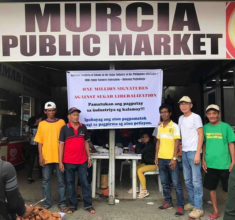 "MURCIA. Nacusip officers Jessie Cervantes and Bonifacio Maylas, and ARBs Sugar Farmers Federation – Kilusang Pagbabago secretary-general Ranie Lava and chairman Aaron Sorbito conduct the ""One Million Signatures Campaign Against Sugar Liberalization"" at the Murcia Public Market Sunday, March 3. (Contributed photo)"