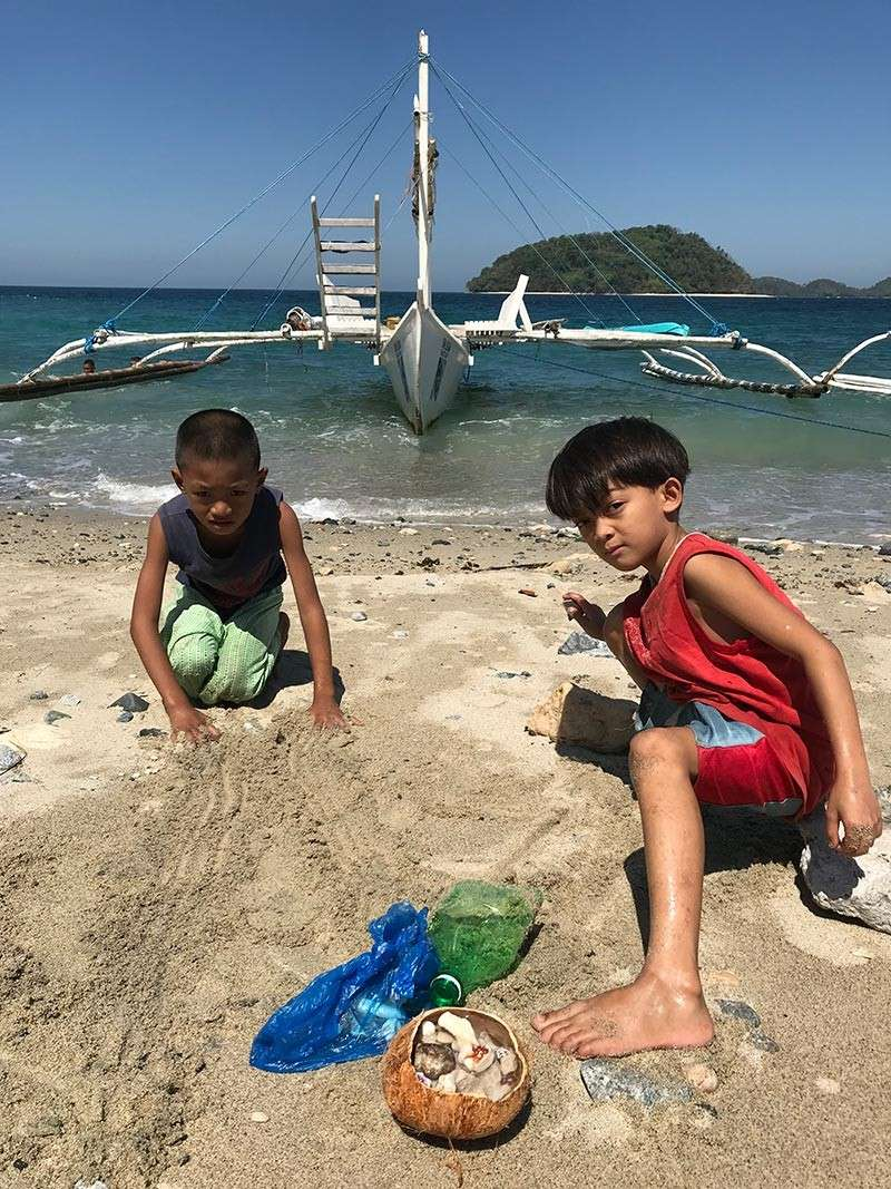 NEGROS. Boys gather shells on the beach where guests take the boat to Danjugan Island shown here partly covered by the smaller but much nearer Agutaya Island. (Photo by Stella A. Estremera)