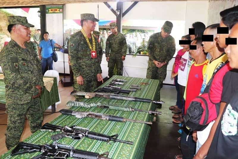 AGUSAN DEL SUR. Former rebels who belong to New People's Army surrender their firearms to the military. (Contributed photo)