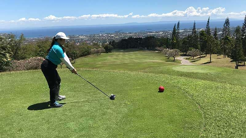 On The Tee. Tiffany addressing her ball on the tee mount of one of the most breathtaking views of Alta Vista.