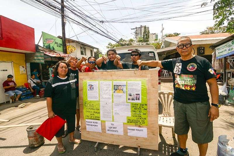 RELIEVED. Members of the Archangels Residents Mergence Inc. (Armi) led by their president, Anne Martel, post their position papers at the entrance of Sitio San Miguel in Barangay Apas, Cebu City as they wait for the court sheriff. (SunStar photo / Amper Campaña)