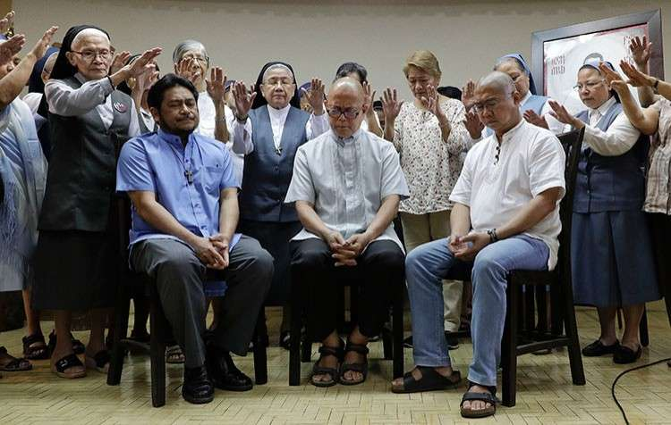 MANILA. Filipino Catholic priest (from left) Fathers Albert Alejo, Robert Reyes and Flavie Villanueva are prayed over by Catholic nuns and  religious leaders after talking to reporters in Quezon City on Monday, March 11, 2019. (AP)