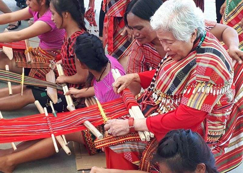 "BAGUIO. DepEd Secretary Leonor Briones tries backstrap weaving or ""laga"" which was included as a specialization under Home Economics in the Technical-Vocational-Livelihood track of a senior high school in the Municipality of Lubuagan in Tabuk City on February 28, 2019. (PIA-CAR photo)"