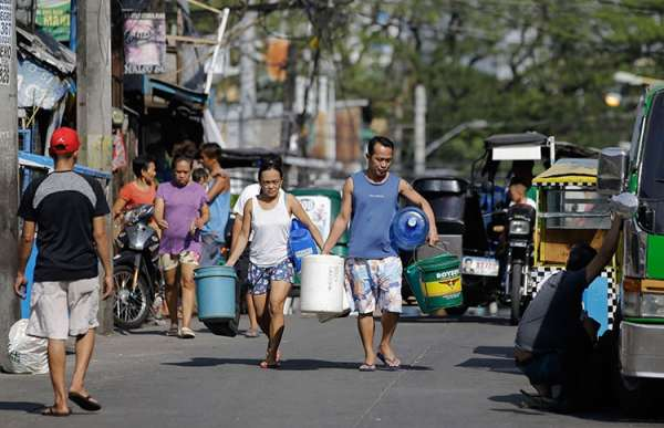 MANILA. A couple carries empty containers looking for places to collect water in Mandaluyong City on Thursday, March 14, 2019. (AP)