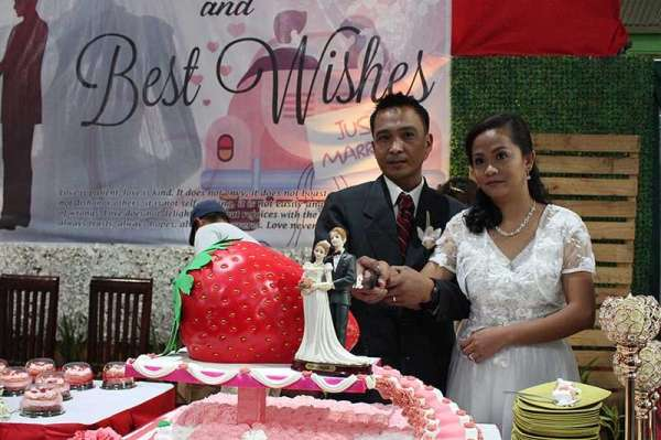 BENGUET. A newlywed couple slices the strawberry cake during the mass wedding of 27 couples at the La Trinidad gymnasium on Wednesday, March 13. (Photo by Jean Nicole Cortes)