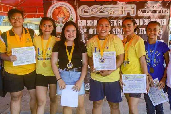 All winners. Gold medalists (from left) Helly Soza, Mary Clair Saga, Niña Abigail Patalinghug, Elreen Ando, RJ Polan and Kicely Lobite are all smiles after winning their division in the Cebu Schools Athletic Foundation Inc. weightlifting event. (SunStar Photo / Arni Aclao)