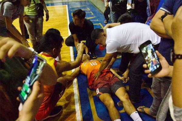 CAGAYAN DE ORO. PCC coach Lantong attends to Ronie Salido after his bad fall during the championship match in the collegiate division of the 14th Loyola Cup on Thursday night at the XU gym. (Jack Biantan)