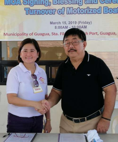 COLLABORATION. House of David Foundation Inc. Chairperson Terry David-Carlos and Guagua Mayor Dante Torres shake hands during the ceremonial agreement signing and turnover of a motorized boat on Friday. (Nicole Renee David)