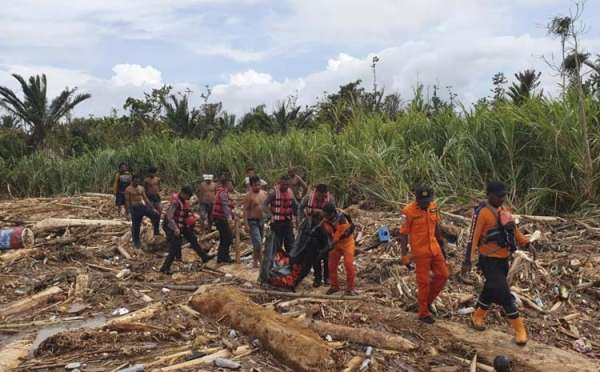 INDONESIA. In this photo provided by National Search and Rescue Agency (BASARNAS), the agency's personnel and police carry the body of flood victim at Sentani, Papua Province, Indonesia, Sunday, March 17. Flash flood and mudslides triggered by days of torrential downpours tore through mountainside villages in Indonesia's easternmost province, killing dozens of people, disaster officials said Sunday. (AP photo)