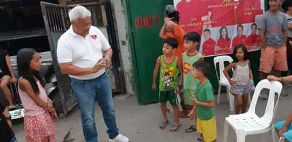 "PAMPANGA. Opposition Councilor and mayoralty aspirant Carmelo ""Pogi"" Lazatin, Jr. on Monday, March 18, showed children in A. Santos, Balibago, Angeles City the proper way to tie a top (trumpo). (Contributed Photo)"