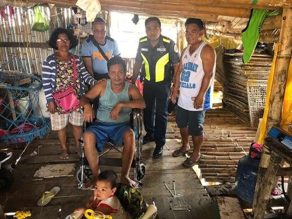 BATAAN. Senior Superintendent Oscar Jacildo, chief of the Police Regional Community Relations Affairs Division (2nd from left), turns over a wheelchair to a man who has been paralyzed for more than 15 years. The man was also one of the fire victims in Barangay Capunitan, Orion, Bataan. (Photo by Ric Sapnu)