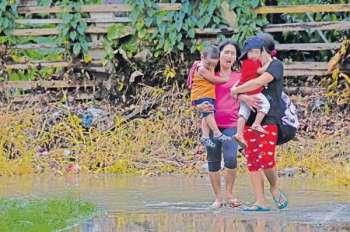 DAVAO. Makita ang duha ka inahan nga nagkugos sa ilang mga anak sa ilang pagbakwit kay mihinay-hinay og taas ang tubig sa sapa sa Balusong River, Matina Crossing, Davao City, kagahapon. (Macky Lim)