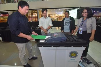 DAVAO. Commission on Elections Davao (Comelec 11) personnel give instructions as they watch a voter cast his sample ballot to the vote counting machine during the Vote Counting Machine Roadshow and Voter's Education Thursday, March 21, at SM City Davao Annex in preparation for the May elections. (Photo by Macky Lim)