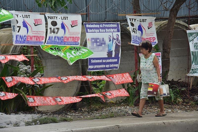 DAVAO. Milabay kilid sa mga campaign posters sa Barangay Ma-a, Davao City ang babaye ug mitan-aw kini sa mga nakasulat sa tarpaulin. Niadtong Martes, gideklara sa Commission on Elections ang tibuok Mindanao isip election hotspot diin ang kontrol anaa gayod sa maong buhatan karong Mayo. (Macky Lim)