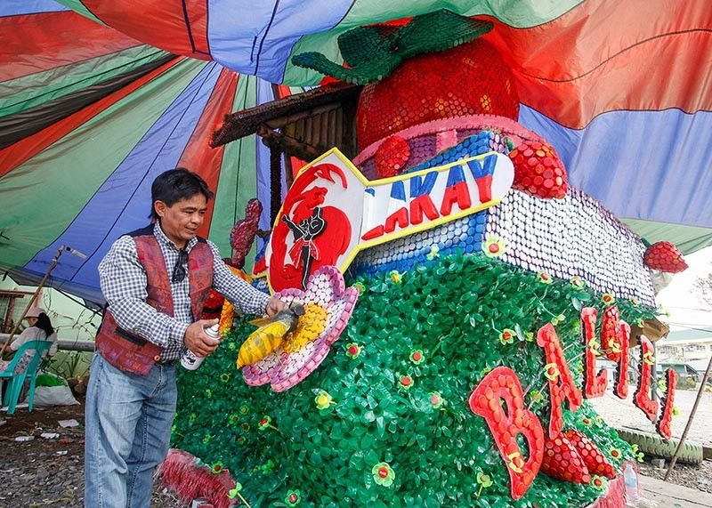 BENGUET. Barangay Balili chief Billy Bilango adds finishing touches to their non-motorized float made of recycled materials as La Trinidad celebrates the highlight of the Strawberry Festival Saturday, March 23. Barangay Balili hopes to defend its title in the non-motorized float category. (Photo by Jean Nicole Cortes)