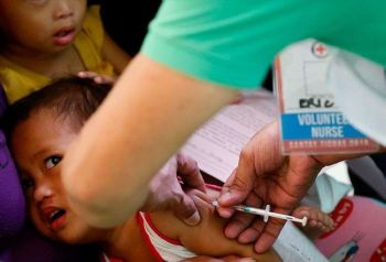 MANILA. In this February 16, 2019, file photo, Philippine National Red Cross and Health Department volunteers conduct house-to-house measles vaccination to children at an informal settlers community in Manila. (AP)