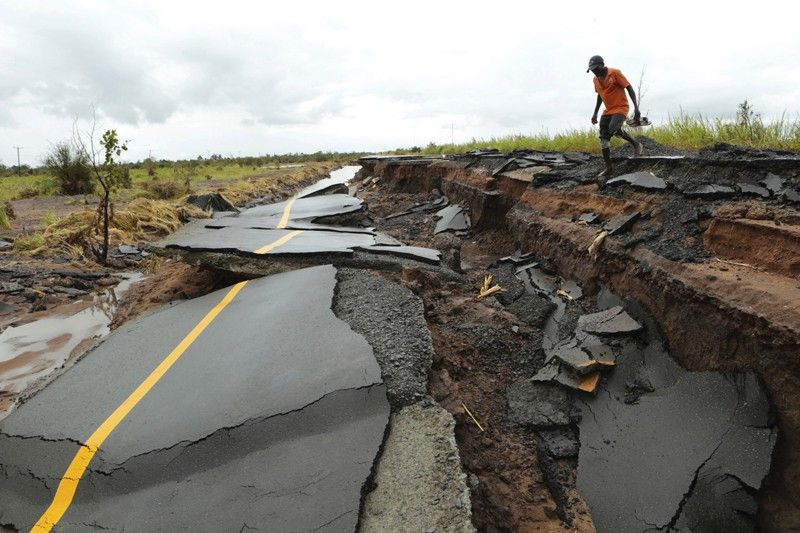 MOZAMBIQUE A man passes through a section of the road damaged by Cyclone Idai in Nhamatanda about 50 kilometres from Beira, in Mozambique, Friday March, 22, 2019. As flood waters began to recede in parts of Mozambique on Friday, fears rose that the death toll could soar as bodies are revealed. (AP)