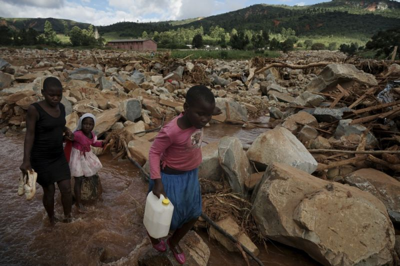 In this photo taken Friday, March 22, 2019, children cross a stream in Chimanimani, Zimbabwe. As flood waters began to recede in parts of Mozambique, Zimbabwe and Malawi fears rose that the death toll could soar as bodies are revealed. (AP Photo)