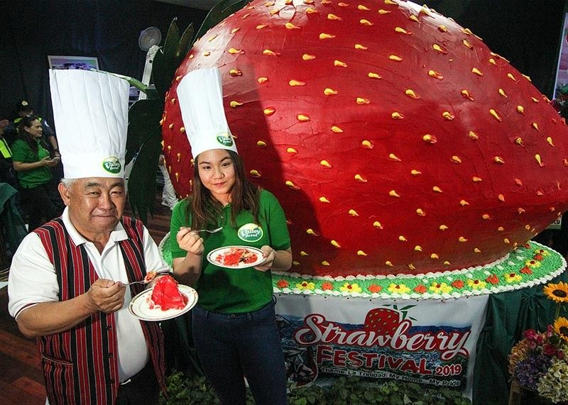 BENGUET. La Trinidad Mayor Romeo Salda and Valley Bread's Angela Espadero partake of the giant strawberry cake weighing 1.6 tons served to 12,000 people on March 23, 2019 at the Lednicky Hall. (Photo by Jean Nicole Cortes)