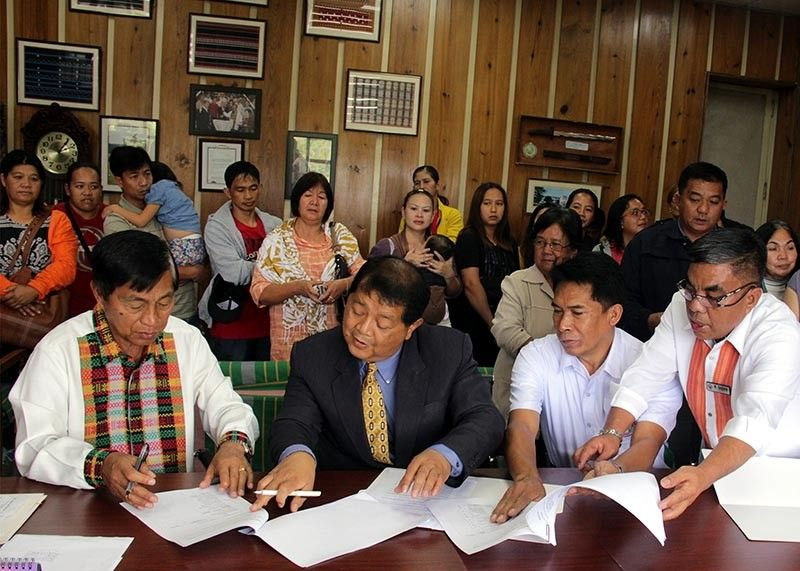 BAGUIO. Mayor Mauricio Domogan with Councilor Edgar Avila and village chief Virgilio Orca Jr. sign the Memorandum Of Agreement on the approved Sangguniang Panglungsod Resolution 0010 series of 2019 for the segregation of lands at North Sanitary Camp. (Photo by Bong Cayabyab)