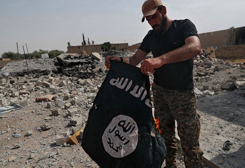 SYRIA. In this July 17, 2017 photo, a fighter of the Christian Syriac militia that battles Islamic State group militants under the banner of the US-backed Syrian Democratic Forces, burns an IS flag on the front line on the western side of Raqqa, northeast Syria. (AP)