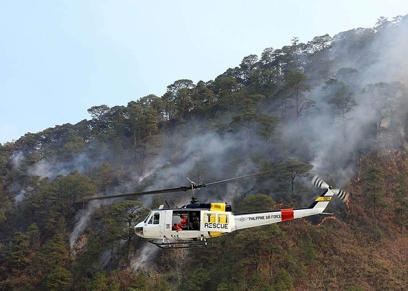BAGUIO. A Philippine Air Force chopper helps in combating forest fires in Benguet. Benguet officials are pushing for better fire prevention programs to avoid more blaze particularly in the forests. (SSB photo)
