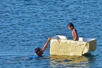 DAVAO. Gilingaw sa amahan ang iyang anak nga nagsakay sa naglutaw nga parte sa refrigerator atol sa ilang pagkaligo sa dagat sa Barangay Talomo, Davao City, kagahapon, Marso 25. (Hulagway kuha ni Macky Lim)